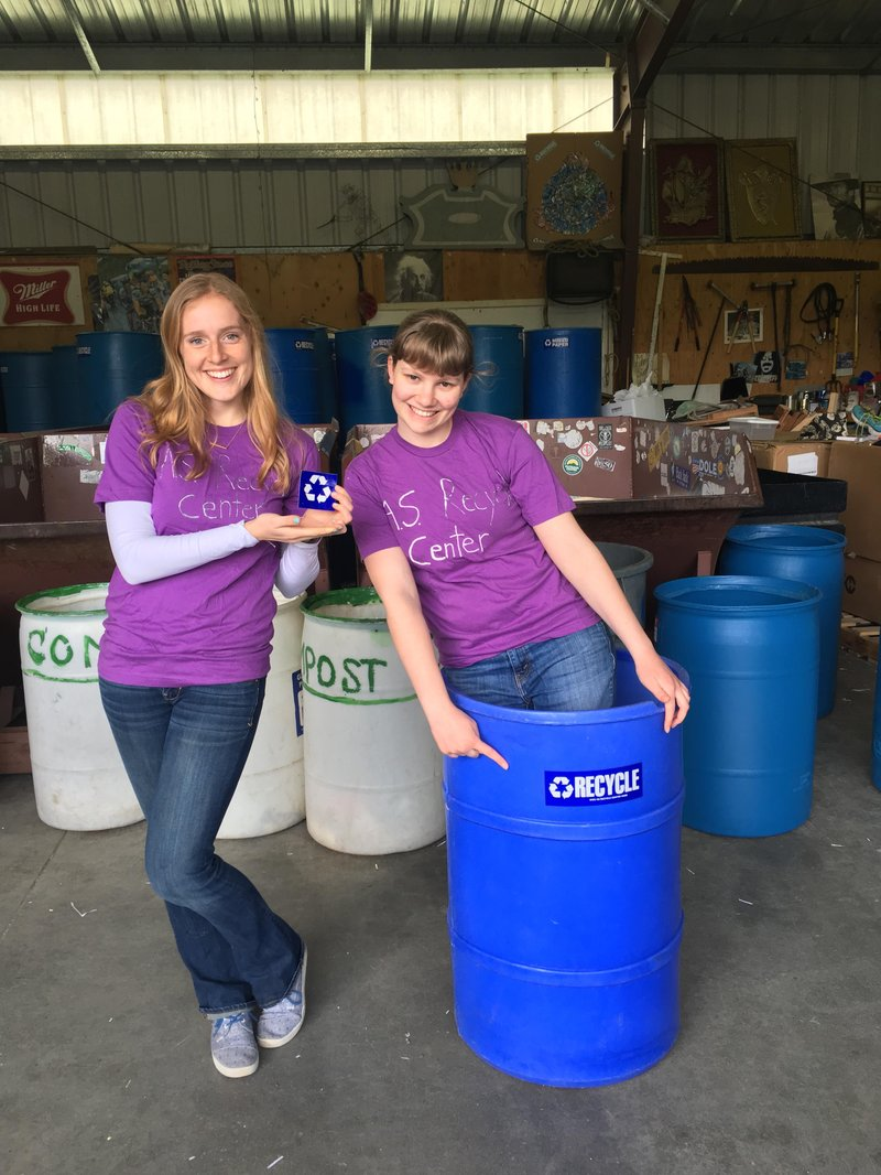 Students with A S Recycle Center shirts hold a recycle sticker and stand in a large blue recycle bin