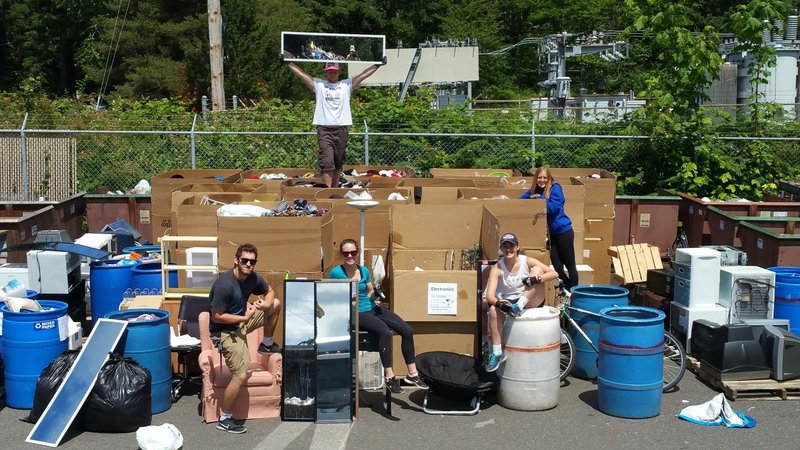 Students posing around large cardboard boxes of clothes, mirrors and assorted household items.