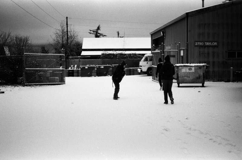 Two students stand outside the compound in the snow