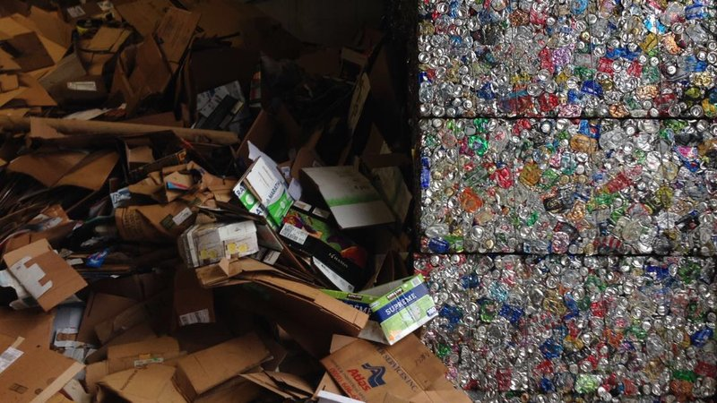 Loose cardboard next to crushed blocks of aluminum cans