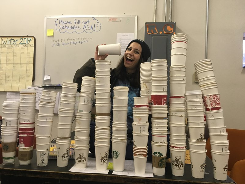 Student pretends to drink from a paper coffee cup. Many stacks of similar cups are in front of them