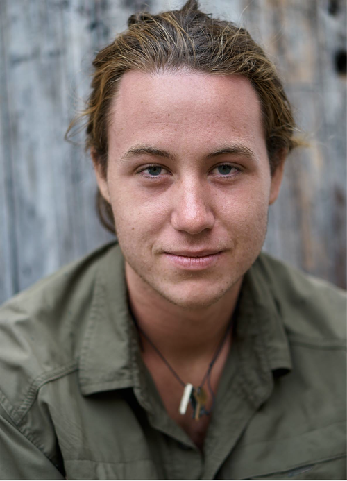 Ben Crandall (his long  brown hair pulled smiling at the camera) with a grey rustic background