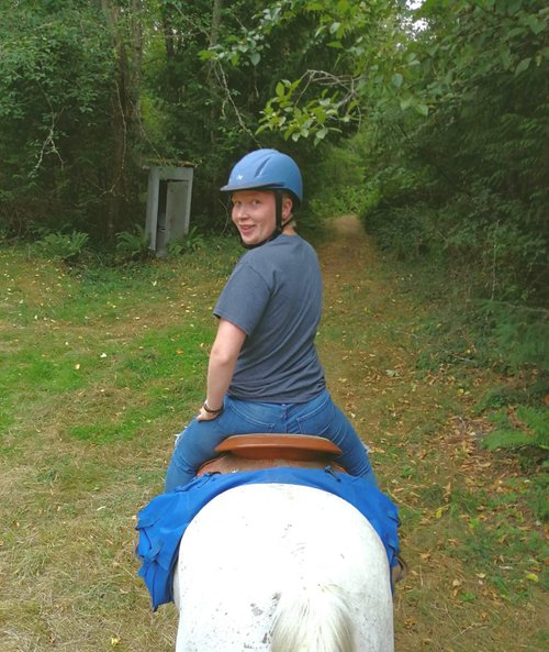 Greyson on horse back turning around to face the camera. He is smiling wearing an english style riding helmet. the horse is walking along a wooded path. There is an old shed that is decomposign in the backround