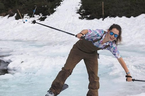 Tara stevens Smiles at the camera as she tries to regain her balance on her skis, her arms are out and she looks like she is about to topple to the right. It also looks like she is skiing on a body of water that has long been covered in snow as the snow she is on is blue and soaked