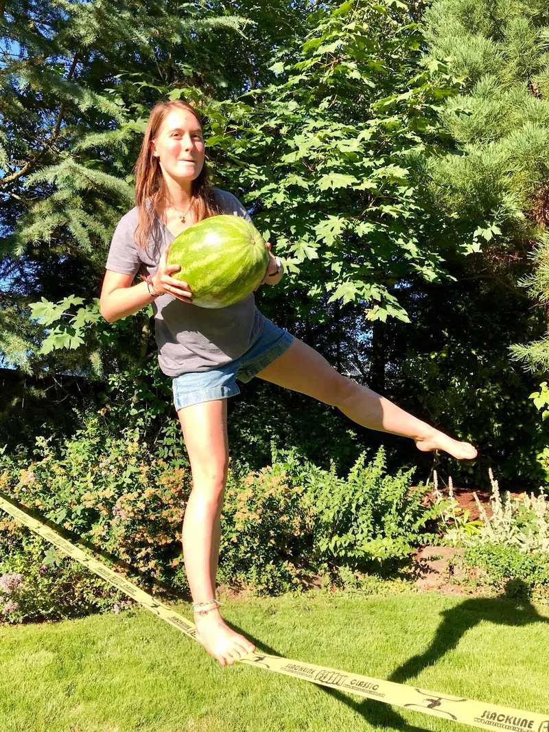 Ella Neumann gives a concentrating smile as she balances on a slackline one legged holding a watermelon. The background is a wooded feild on a sunny day