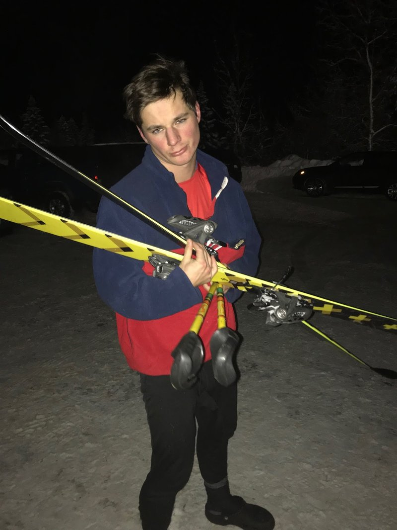 Grant Rienstra looks disapointedly at the camera as he holds his skiis and poles in a messy bunch that will surely fall appart soon. He is in a dark and snowy parkinglot with crocs on