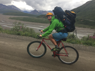 Gus Wimberger looks at the camera in goofy excitment as he bikes up hill with a backpack that is about the same size as he is. the background is a riverbed in the dry season when the riverrocks are showing