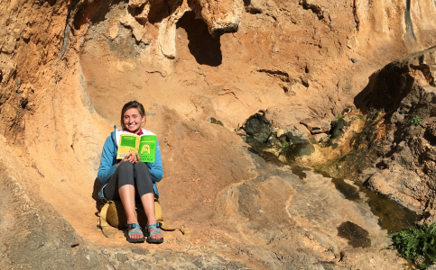 Mayah Demartino sitting in a rock shelter with a book in hand smiling at the camera