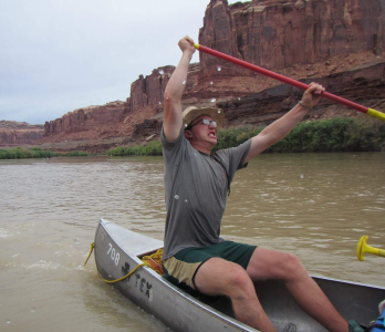 Owen Merritt is raising his oar above his head ready to strike the water, pure consintration in his face as he canoes down a dessert river brown from the erosion that has caused the many towers and clifs that take up the background