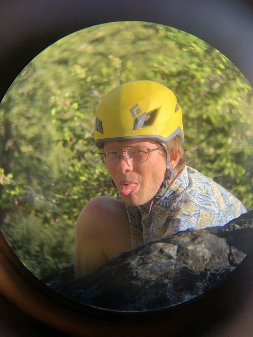Tanner Randall-Gosselin with a helmet on and in a hawaiian shirt (sticking his tongue out at the camera) a rock is between him and the camera and green folliage is behind him