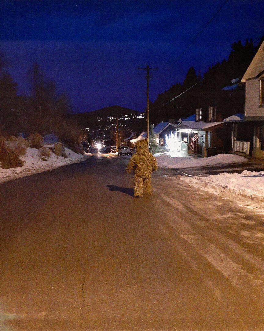 Image of figure wearing the artwork walking along a street at night.png